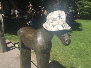Solen gassade. Någon, troligen ett barn, hade skänkt en hatt (av typen Svensson-melitta) till en av hästskulpturerna i Vasaparken.