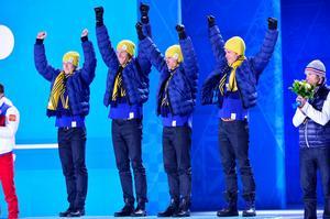 Lars Nelson, Daniel Rickardsson, Johan Olsson och Marcus Hellner tar emot sina guldmedaljer under prisceremonin i Sotji 2014. Bild: Daniel Stiller/Bildbyrån.