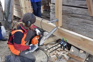 Malin Mattson från Mariehamn använder motorsåg för att passa in de nya stockarna i den gamla stommen.