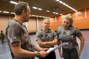 Jimmy Kocsis, kurschef genom Försvarsutbildarna, går igenom information om fystestet tillsammans med Ida Danielsson och Tuva-Lisa Höglund.