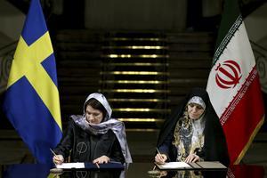 Minister  Ann Linde (S) skriver på affärsdokument i Teheran tillsammans med Shahindokht Molaverdi förra året. Så rasade en debatt här hemma om varför en svensk minister bär slöja.
