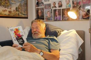 Bosse Kärvinge med en god bok, sina nio barnbarn och en tavla med Stockholms skärgård.