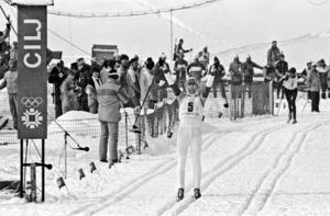 Den svenska slutmannen Gunde Svan höjer armarna i skyn när han går över mållinjen som segrare i herrarnas stafett i vid de olympiska vinterspelen i Sarajevo 1984. Tvåan Sovjet skymtas i början av upploppsrakan. Bild: Jan Collsiöö/TT.