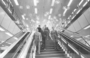 Försäljningen i nya Domus 1971 sker i två plan, mellan vilka man kan ta sig i hissar, rulltrappor eller - som herrarna på bilden - till fots. Närmast går varuhuschefen Karl Ericsson, föreningsledaren Arne Jägmo och marknadschefen Sven-Erik Svensson.  Foto: VLT:s arkiv