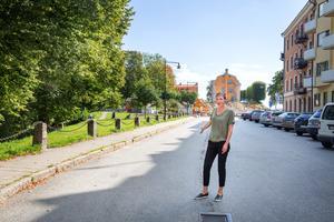 Stina Norrbom står ungefär dit stenpollarna med kedjor som skymtar till vänster ska flyttas. Till höger om henne försvinner parkeringsplatserna och Västra Kanalgatan blir smalare. Till vänster om henne ska nya infarten till Kringlangaraget börja.