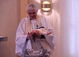Prästen Markus Frank döper Alfred, som ännu inte har reagerat på vattenbegjutningen.