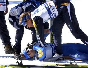 Sveriges fjärdeman på stafetten i Val di Fiemme 2003, Jörgen Brink, har med nöd och näppe tagit sig i mål som trea. Först framme att kontrollera statusen på Brink är Mathias Fredriksson. Bild: Anders Wiklund/Scanpix
