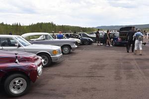 Massor av bilar och besökare på flygfältet.