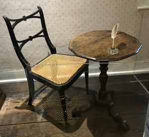 Det var vid det här lilla bordet Jane Austen satt och skrev på förmiddagarna efter flytten till Chawton 1809.  Någonting känner jag när jag står inför det lilla bord vid vilket de här eviga berättelserna faktiskt mejslades ut, ord för ord. Vördnad kanske. Skrivlådan med lock som hon ställde ovanpå förvaras på British Library.