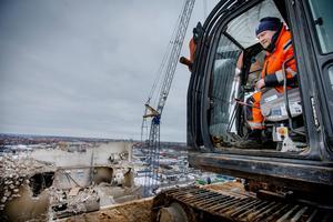 Med en kraftig sax krossar grävmaskinen betongen i den från början 65 meter höga silon bit för bit. Jonas Persson från rivningsföretaget Delete, 45 meter över marken på taket av silon på Aspholmen i Örebro.