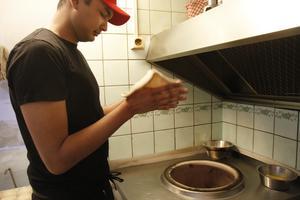 Kocken Tanvir Ahmed Utchash tar en bit naandeg och plattar ut den med händerna i några snabba rörelser.