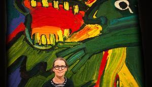 Konstpedagog Maria Sundström framför en av de vävda gobelängerna med motiv av Bengt Lindström.