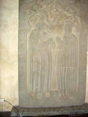 Makarna Lars och Margit Ingwaldsson vackert avbildade i naturlig storlek i kalksten. Tittar man närmare på gravhällen syns Bråsta-Lasses träben tydligt under den fotsida manteln. Foto: Åke Johansson