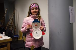 Simone Sandelin Norén håller upp sina konstverk. Både snögubben och medaljen tillverkade hon under Vinterdagen.