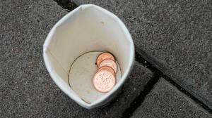 Några mynt i tiggarens pappmugg. Foto: Niklas Norén