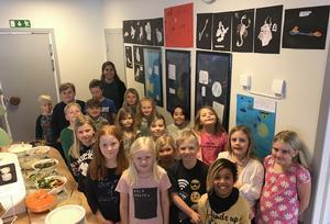 Eleverna visar stolt upp  en del av utställningen i Kyrkskolans matsal.