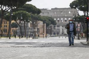 En man går längs en folktom gata i Rom. I bakgrunden skymtar Colosseum.