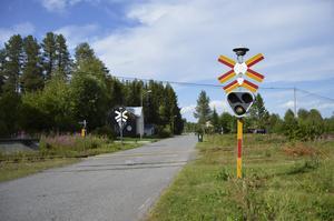 Vid järnvägsövergången ner mot stationsområdet får Märit för första gången se tåget.