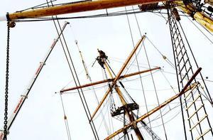 Skeppsansvarige Magnus Lagerkvist och riggarbetaren Karl-Oskar Momark befinner sig minst 20 meter upp i luften när de ska fästa den nyrenoverade toppmasten på Briggen Gerda.