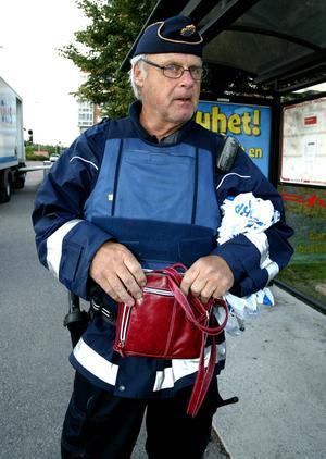 Bengt Lundgren, insatsledare, visar upp den väska som hittades inne i restaurangen. Foto: Thomas Isaksson