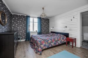 Mörkare tapet med vita blommor i ett av sovrummen. Foto: Marijo Grgic/ Bostadsfotograferna