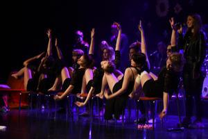 De synkroniserade dansarna i rörelse till sång av en av musikesteterna.
