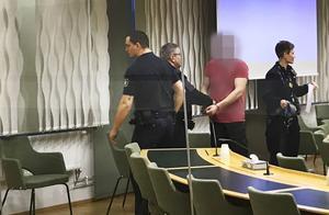 Den misstänkte mannen förs ut ur rättssalen av häktesvakter efter  förhandlingen.