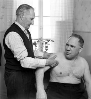 Per Olof Strand tog emot tusentals ledbrutna patienter i sitt hem i Hedesunda. Här är det byns järnhandlare, Folke Karlsson, som grinar illa när en urhoppad ledkula sätts på plats. Foto: Lars Rosenblom/Arbetarbladet, 1965