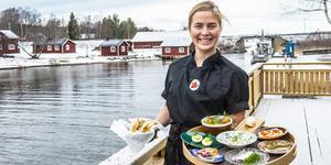 Amanda Samuelsson med olika sillar, ägg, lax och annat som hör påskbordet till på bryggan utanför restaurangen.