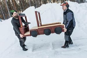 Stefan Mattsson och Torbjörn Linde bär ut en lekbil i trä. Torbjörn började jobba på Hugos Trä 1984 och har varit längst på företaget. Han har även gått skola i lokalerna. – Jag trivs jättebra och jobbet blir aldrig monotont. Vi gör olika saker hela tiden, förutom bilarna som är ständigt återkommande, säger han.