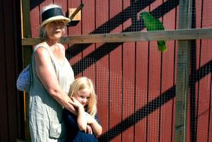 Frida och Tyra Hassberg hälsar på papegojan vid Backetjärn i samband med sin badutflykt.