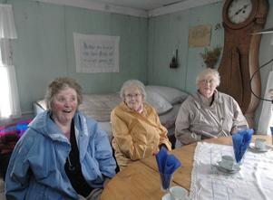 Astrid Jonsson, Ann-Marie Ehn och Svea Höglund sitter och trivs i den gamla fäbodstugan.