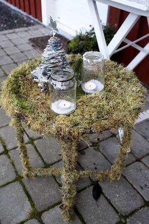 Bordet är ett rostigt gammalt utebord som har mossbeklätts med hjälp av fiskelina.