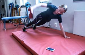 Hanna Wahlqvist kör ett pass i gymmet med hjälp av en tränings-app på mobilen.