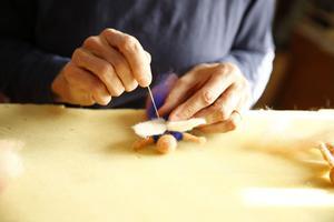 ... Innan man fäster vingar eller luva på figuren med hjälp av nålen.