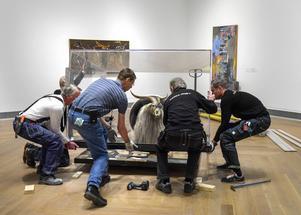 Tekniker på Moderna Museet lyfter på den monter som skyddar Robert Rauschenbergs konstverk