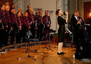Sångsolisten Angelica Engstad och Lars Trygg, påklarinett, tillsammans med en del av Saxdalens manskör.