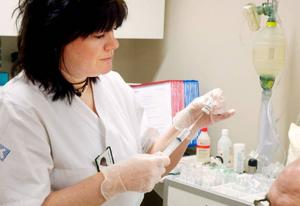 Distriktssköterskan Karin Berg förbereder Göstas behandling.Foto: Sandra Högman