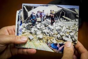 Hamadamin Sadiq visar fotografier från familjens hus hemma i Irak. På bilden står barnen på en hög med betongsten och bråte, det som var deras hem är nu en sönderbombad ruin.
