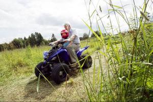 Morfar Ulf Pettersson tar sitt barnbarn Benjamin på en tur med fyrhjulingen.