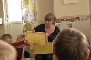 Bisyssla. Eva Sääv visar barnen hur ramarna ser ut som bina bildar sin honung i. Wilma Nyberg och Ebba Johansson får titta.