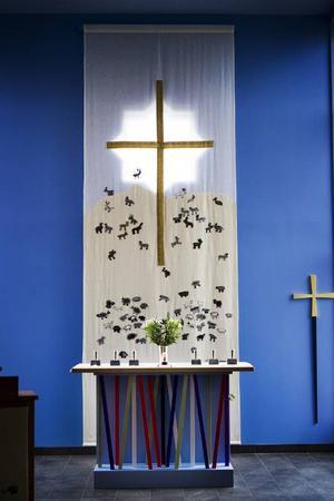 Altaret och väven. Två ting som sätter avtryck i hela kyrkorummet. Altaret med sin mångskiftande symbolik och väven där hundratals skolbarn involverades och fick sätta sin prägel.