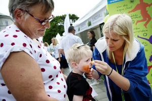 Trevor Rex, 3, 5 år, i knät på Kerstin Johansson förvandlas till en tiger med hjälp av Ida Dahlström som är en av sommarentreprenörerna på Gatufesten.