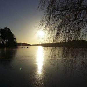 Solen speglar sig i den blanka isen på Ösjön vid Tomnäs.