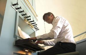 Lars Andersson vid den gamla Ek-orgeln på läktaren i Stöde kyrka.