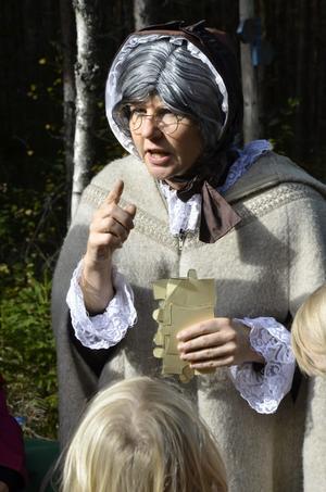 Samlar in. Gertrud (Mari Andersson-Jansson) samlar in pusselbitarna till Christopher Polhems ritning.