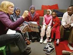 Författaren Marie-Louise Andersen läser högt ur �Majken och Melker besöker Amir i Gävle�, medan tolken Fatima Nuur (till höger om henne) översätter till somaliska. Mariam Sheik, systrarna Mariam och Mona Bisre och pappa Hassan Hussein lyssnar. Foto: Lars Wigert
