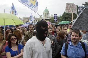 En maskerad man tillsammans med en rad andra demonstranter vid en demonstration i Belgrad i juni. Arkivbild.   Marko Drobnjakovic/TT/AP