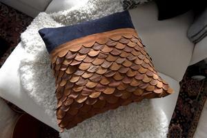 Monica Karlstein har limmat fast läderdekorationer på ett färdigt kuddfodral köpt i butik. Genom att välja två olika typer av läder och varva avig- och rätsidor ser det ut som att mönstret är skapat av fyra olika sorters läder.