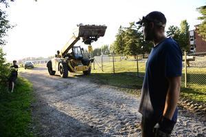 Traktorn kör tunga stora naturstenar som ska tippas ner i bäcken.